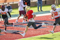 National Team quarterback Ian Book of Notre Dame (12) runs in a touchdown during practice for the NCAA Senior Bowl college football game in Mobile, Ala., Thursday, Jan. 28, 2021. (AP Photo/Matthew Hinton)