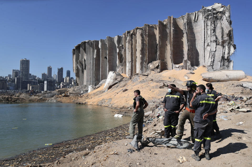 A rescue team surveys the site of this week's massive explosion in the port of Beirut, Lebanon, Friday, Aug. 7, 2020. Three days after a massive explosion rocked Beirut, killing over a hundred people and causing widespread devastation, rescuers are still searching for survivors and the government is investigating what caused the disaster. (AP Photo/Thibault Camus)
