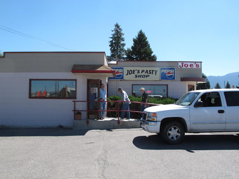 This July 20, 2013 photo shows customers entering Joe's Pasty Shop in Butte, Mont. The shop is one of a handful that serve the meat-and-potato pie that immigrant miners brought a century ago and has remained a part of Butte's culinary culture. (AP Photo/Matt Volz)