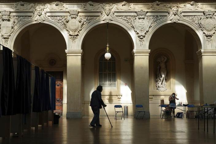 A voter exits a voting booth as they vote for the regional elections in Lyon, central France, Sunday, June 20, 2021. The elections for leadership councils of France's 13 regions, from Brittany to Burgundy to the French Riviera, are primarily about local issues like transportation, schools and infrastructure. But leading politicians are using them as a platform to test ideas and win followers ahead of the April presidential election. (AP Photo/Laurent Cipriani)