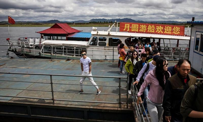 Chinese tourists disembark from a boat on the Yalu river.