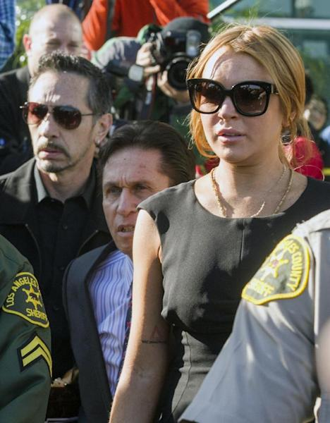 Lindsay Lohan, right, her new attorney Mark Heller, background center, leave a Los Angeles court, Wednesday, Jan. 30, 2013, in a case filed over the actress' car crash last June. A judge has delayed Lohan's trial on three misdemeanor counts. She pleaded not guilty to lying to police, reckless driving and obstructing officers from performing their duties. (AP Photo/Damian Dovarganes)