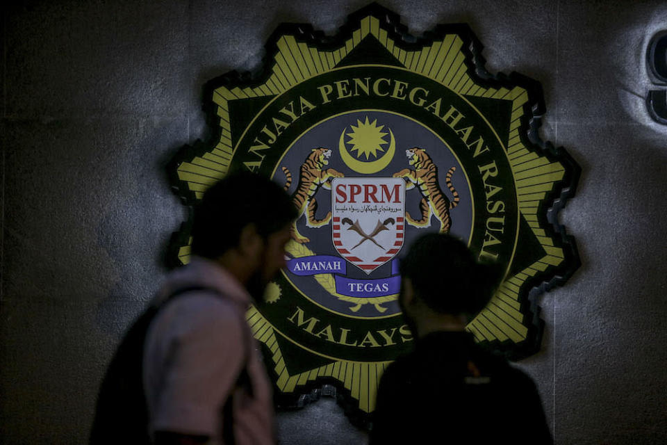 Two members of the media stand against the backdrop of the MACC  logo in Putrajaya July 3, 2018. — Picture by Hari Anggara