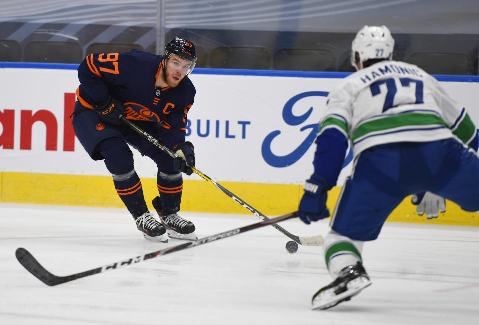 Edmonton Oilers' Connor McDavid (97) looks to get past Vancouver Canucks' Travis Hamonic (27) during the second period of an NHL hockey game Wednesday, Jan. 13, 2021, in Edmonton, Alberta. (Dale MacMillan/The Canadian Press via AP)