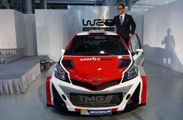 "Toyota Motor Corp President Akio Toyoda poses for pictures on the top of the ""Yaris WRC"", a vehicle being developed for the FIA World Rally Championship (WRC) during a news conference to announce its return to WRC in 2017, in Tokyo January 30, 2015. REUTERS/Yuya Shino (JAPAN - Tags: SPORT MOTORSPORT BUSINESS)"