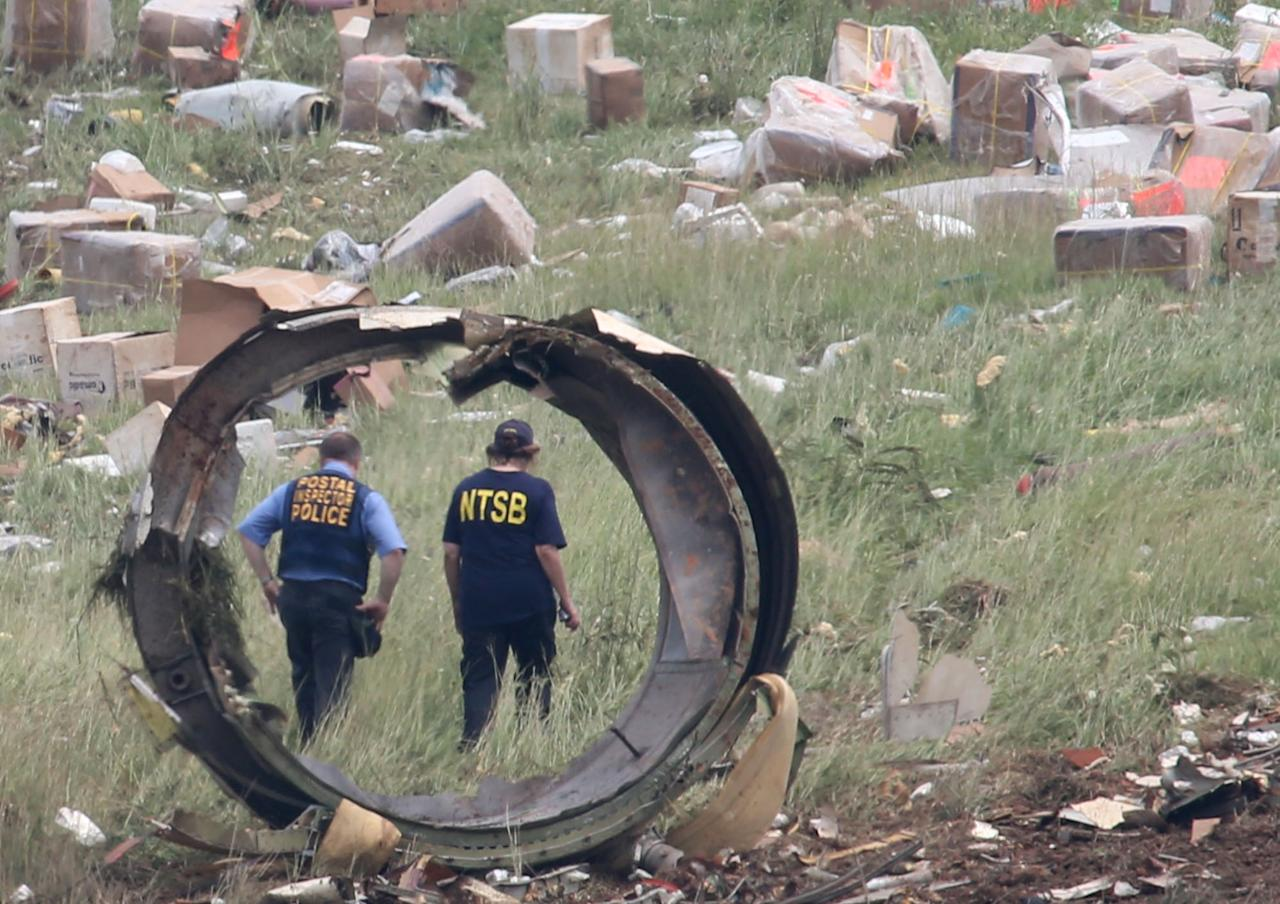 A postal Inspector officer and a NTSB investigator are seen through a section debris of a UPS A300 cargo plane after it crashed on approach at Birmingham-Shuttlesworth International Airport this morning Wednesday August 14, 2013 in Birmingham, Ala. The two pilots aboard the aircraft were killed. (AP Photo/Hal Yeager)