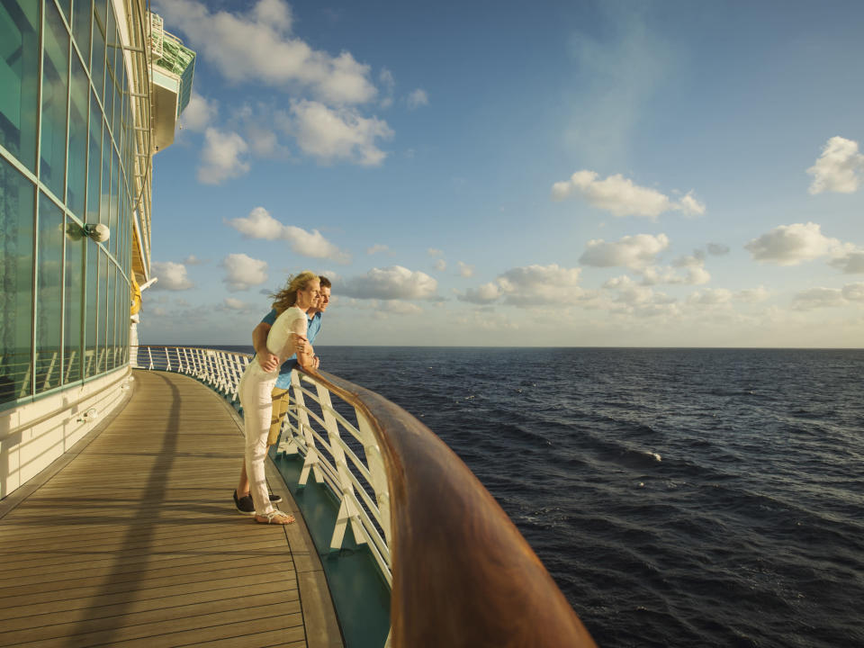 Couple admires the ocean view from the deck of a cruise ship. (Getty)