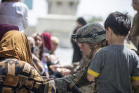 In this image provided by the U.S. Marine Corps, a corpsman with the 24th Marine Expeditionary Unit (MEU) checks the well-being of evacuees' during an evacuation at Hamid Karzai International Airport in Kabul, Afghanistan, Friday, Aug. 20, 2021. (Sgt. Samuel Ruiz/U.S. Marine Corps via AP)