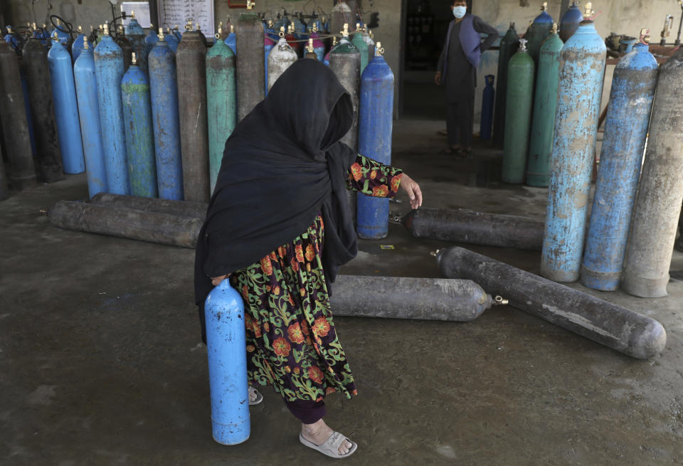 A woman carries an oxygen cylinder from a privately owned oxygen factory, in Kabul, Afghanistan, Saturday, June 19, 2021. Health officials say Afghanistan is fast running out of oxygen as a deadly third surge of COVID worsen. (AP Photo/Rahmat Gul)