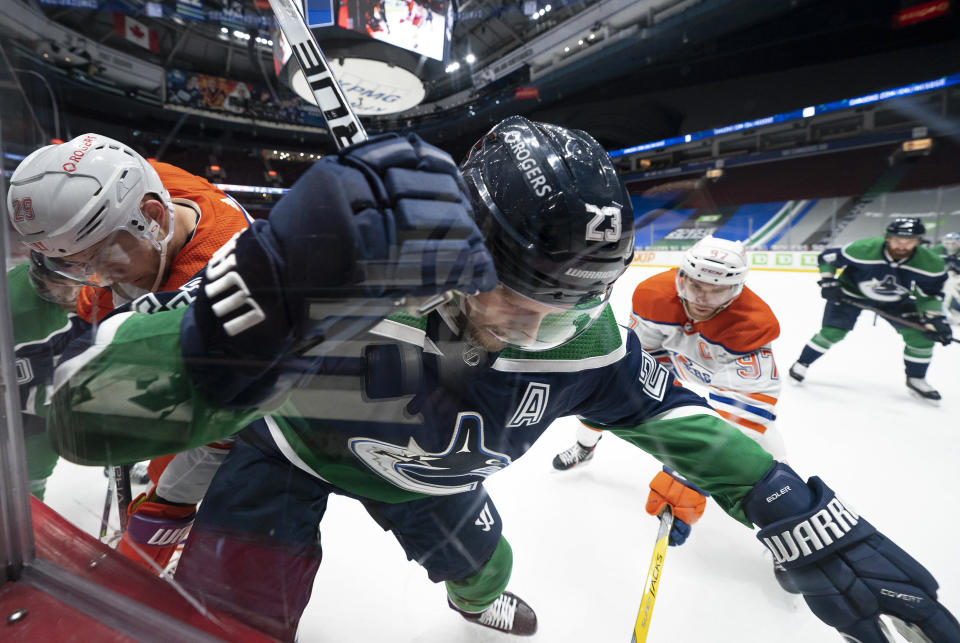 Vancouver Canucks defenseman Alexander Edler (23) competes for control of the puck with Edmonton Oilers' Leon Draisaitl (29) and Connor McDavid (97) during the third period of an NHL hockey game Tuesday, Feb. 23, 2021, in Vancouver, British Columbia. (Jonathan Hayward/The Canadian Press via AP)