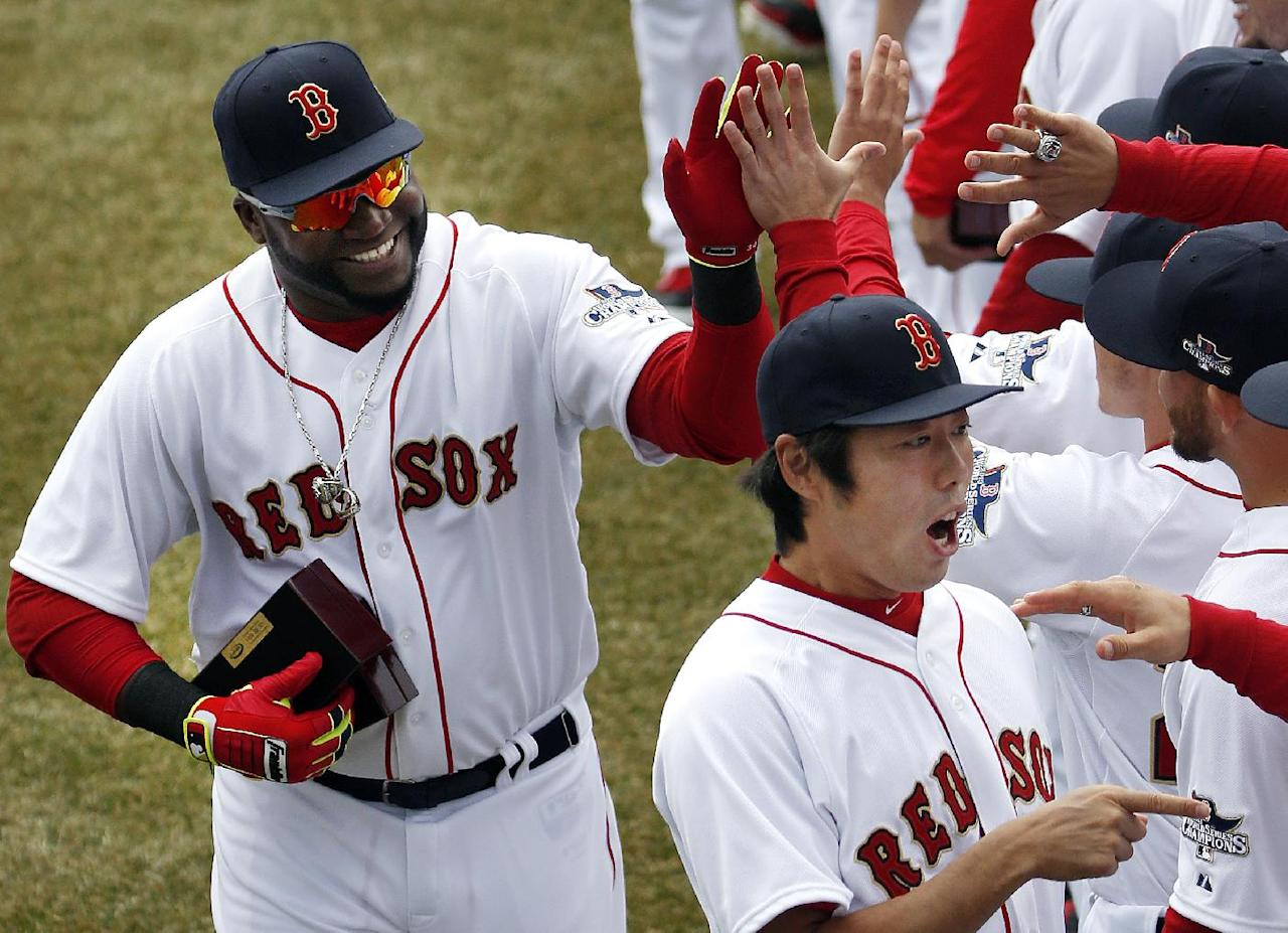 Boston Red Sox designated hitter David Ortiz, left, and relief pitcher Koji Uehara, lower right, celebrate with teammates after receiving their 2013 World Series rings at Fenway Park in Boston, Friday, April 4, 2014, during home opening day ceremonies prior to a baseball game between the Boston Red Sox and the Milwaukee Brewers. (AP Photo/Elise Amendola)
