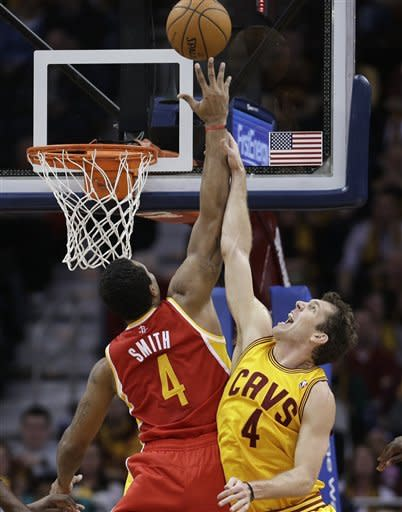 Cleveland Cavaliers' Luke Walton, right, and Houston Rockets' Greg Smith go up for a rebound during the second quarter of an NBA basketball game Saturday, Jan. 5, 2013, in Cleveland. Walton was called for a foul. (AP Photo/Tony Dejak)