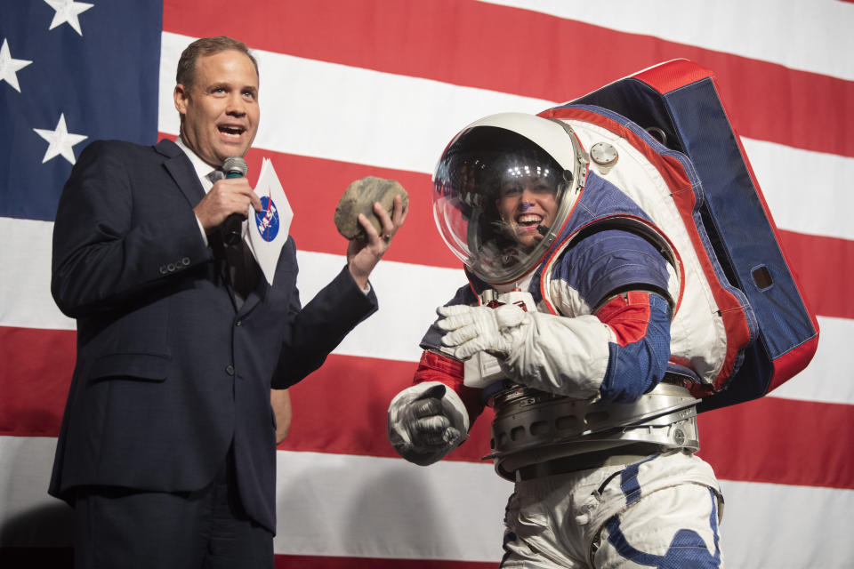 NASA administrator Jim Bridenstine holds a rock handed to him by Kristine Dans during a demonstration of the Exploration Extravehicular Mobility Unit (xEMU), one of two NASA spacesuit prototypes for lunar exploration on Tuesday, Oct. 15, 2019, at NASA Headquarters in Washington. (AP Photo/Kevin Wolf)