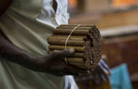 """A worker carries hand-twisted cigars in his hand at the La Corona Tobacco factory where a worker reads to them in Havana, Cuba, Tuesday, June 29, 2021. Readers are on staff at the state-owned factories, a job the government has declared a """"cultural patrimony of the nation,"""" and workers elect the readers and vote on what will be read. (AP Photo/Ismael Francisco)"""