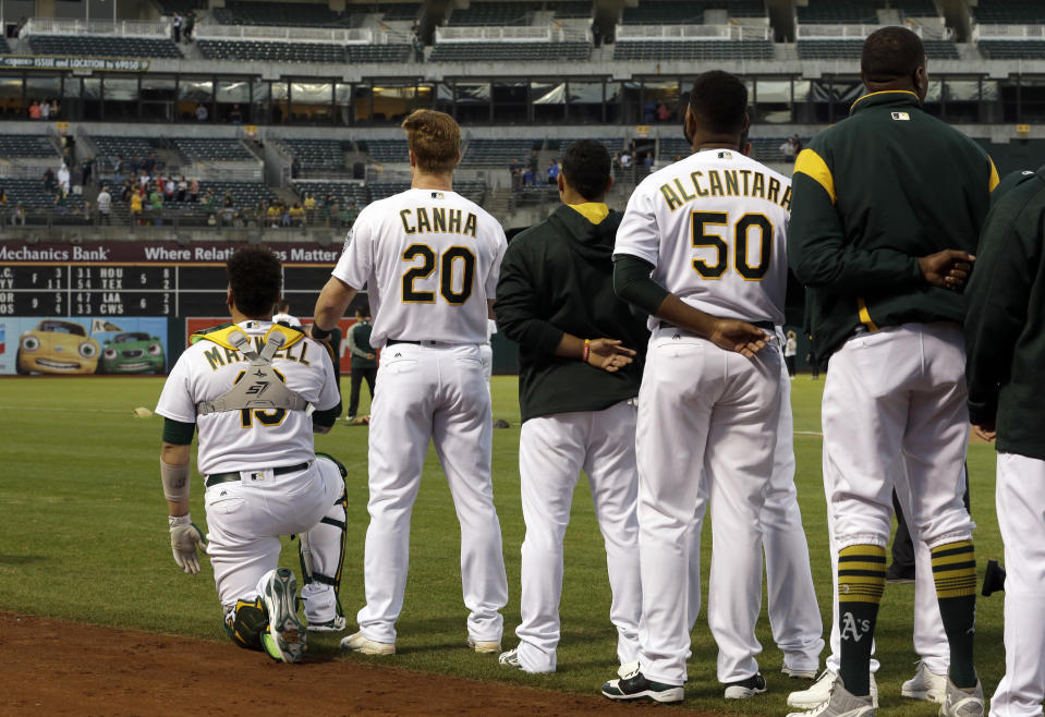 Oakland Athletics' Mark Canha (20) places his hand on the shoulder of Bruce Maxwell as Maxwell kneels during the national anthem for the third consecutive day, prior to the team's baseball game against the Seattle Mariners on Monday, Sept. 25, 2017, in Oakland, Calif. (AP Photo/Ben Margot)