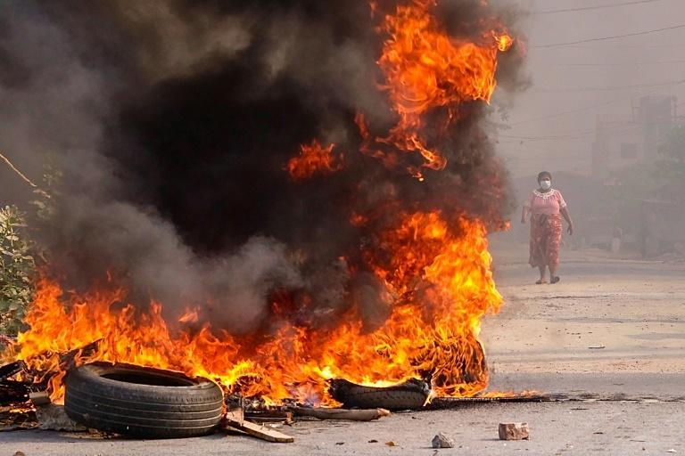 A woman walks near burning barricades in Mandalay during a crackdown by security forces on demonstrations against the military coup in Myanmar