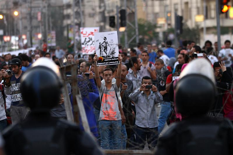 """Demonstrators protest in front of the presidential palace in Cairo, Egypt, Saturday, April 26, 2014. Hundreds of secular-minded activists and protesters rallied in front of the presidential palace Saturday, demanding the interim president abolish a disputed protest law used extensively over the past months to jail and prosecute activists, including leading figures of the 2011 uprising that toppled longtime autocrat Hosni Mubarak. Arabic in poster in center reads: """"Drop law and get them out of prison""""."""