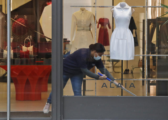 A woman wearing a face covering due to the COVID-19 pandemic cleans inside a shop during lockdown in London, Wednesday, Feb. 17, 2021. (AP Photo/Frank Augstein)