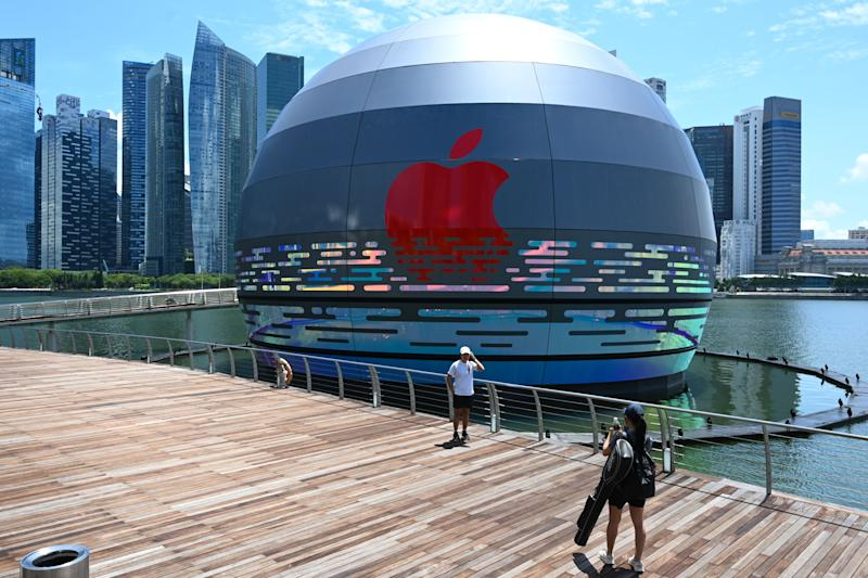 A woman takes a photograph for a friend in front of the new Apple store, located in the water in front of the Marina Bay Sands, in Singapore on August 24, 2020. (Photo by Roslan RAHMAN / AFP) (Photo by ROSLAN RAHMAN/AFP via Getty Images)
