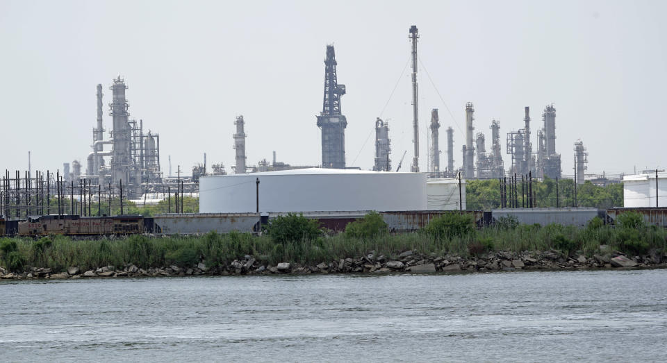 """Storage tanks at a refinery along the waterway are shown Thursday, July 26, 2018, in Port Arthur, Texas. The oil industry wants the government to help protect some of its facilities on the Texas Gulf Coast against the effects of global warming. One proposal involves building a nearly 60-mile """"spine"""" of flood barriers to shield refineries and chemical plants. Many Republicans argue that such projects should be a national priority. But others question whether taxpayers should have to protect refineries in a state where top politicians still dispute whether climate change is real. (AP Photo/David J. Phillip)"""