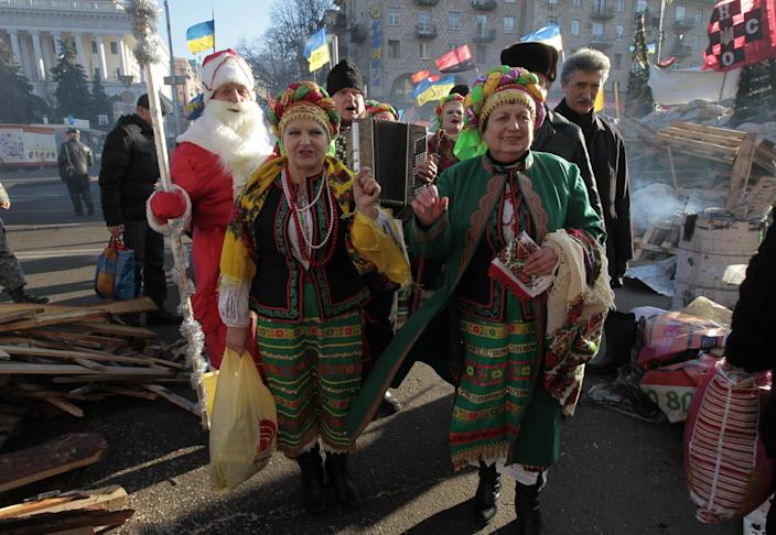 People dressed in traditional Ukrainian clothes and a man dressed as Grandfather Frost (the local equivalent of Santa Claus) sing Christmas carols during a pro-European Union rally in Independence Square in Kiev, Ukraine, Thursday, Dec. 26, 2013. (AP Photo/Sergei Chuzavkov)