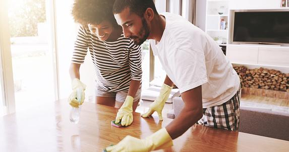 Photo of a male and female cleaning the dining table together