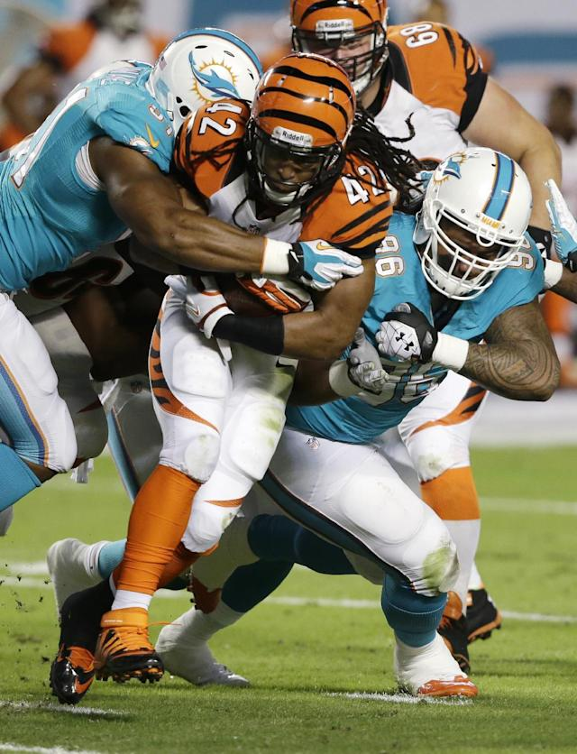Miami Dolphins defensive tackle Paul Soliai (96) and defensive end Cameron Wake (91) tackle Cincinnati Bengals running back BenJarvus Green-Ellis (42) during the first half of an NFL football game, Thursday, Oct. 31, 2013, in Miami Gardens, Fla. (AP Photo/Wilfredo Lee)