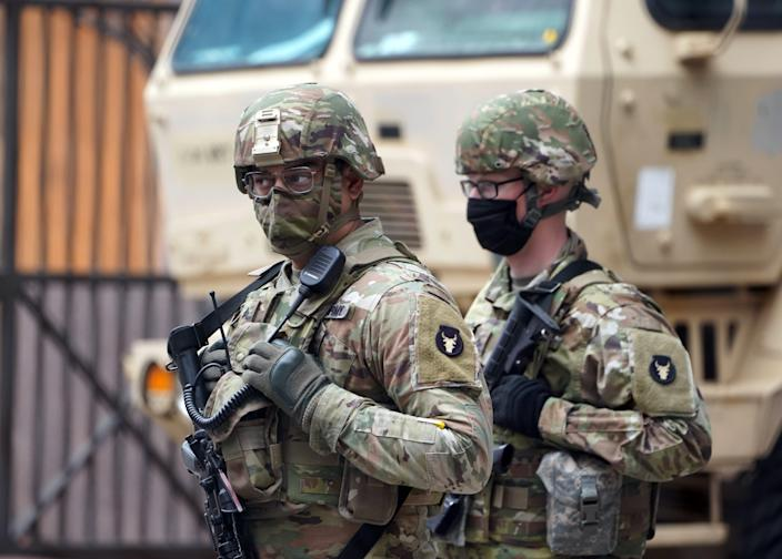 Member of the Minnesota National Guard patrol an intersection in downtown Minneapolis shortly before jurors were set to begin deliberations in the murder trial of former police officer Derek Chauvin.