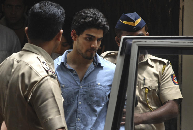 Suraj Pancholi, the son of Bollywood couple Aditya Pancholi and Zarina Wahab is escorted by police as he leaves after appearing before a court in Mumbai, India, Tuesday, June 11, 2013. Pancholi, has been arrested on suspicion of abetting the suicide of his girlfriend, actress Jiah Khan, police said. Khan, 25, committed suicide at her home in Mumbai last week. (AP Photo)