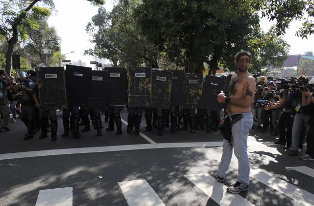 Media take pictures as a demostrator stands in front of Military police near Caarao metro station during a protest against the 2014 World Cup, in Sao Paulo June 12, 2014. REUTERS/Nacho Doce (BRAZIL - Tags: SPORT SOCCER WORLD CUP POLITICS CIVIL UNREST MEDIA)