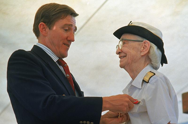 FILE - In this Aug. 14, 1986 file photo, Admiral Grace Hopper is honored by Navy Secretary John Lehman, during her retirement ceremony aboard the USS Constitution, in Boston, Mass. On Saturday, Feb. 11, 2017, Yale University said it is renaming Calhoun College after Hooper, a trailblazing computer scientist, a mathematician who earned Yale degrees in the 1930s, invented a pioneering computer programming language and became a Navy rear admiral. (AP Photo/Peter Southwick)