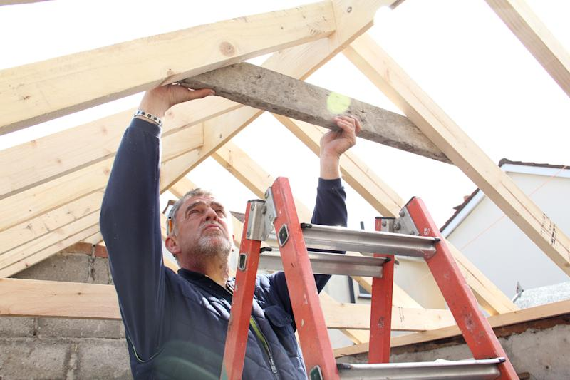 Man measures timber for roof