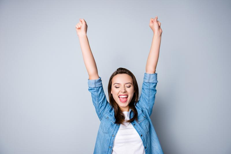 Amazed brunette young business woman in casual shirt is gesturing victory with her raised hands.
