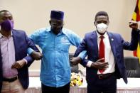 Ugandan opposition presidential candidate Robert Kyagulanyi, also known as Bobi Wine, poses with other opposition leaders Patrick Oboi Amuriat and Mugisha Muntu during a press conference in Kampala
