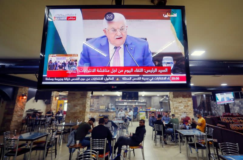 A screen displaying a live broadcast of the Palestinian President Mahmoud Abbas's speech during a meeting discuss upcoming elections, is seen in a coffee shop in Ramallah