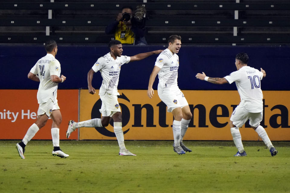 Los Angeles Galaxy's Kai Koreniuk, second from right, celebrates his goal with teammates during the second half of an MLS soccer match against the Vancouver Whitecaps, Sunday, Oct. 18, 2020, in Carson, Calif. (AP Photo/Marcio Jose Sanchez)