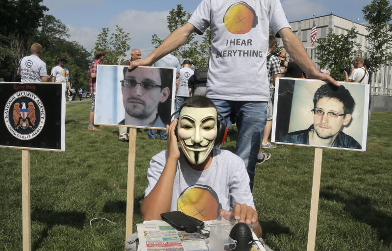 Activists of Ukraine's Internet party, one of them acting as a CIA agent making telephone taps, demand the American authorities stop the pursuit of National Security Agency leaker Edward Snowden at an action of protest near the US Embassy in Kiev, Ukraine, Thursday, June 27, 2013. (AP Photo/Efrem Lukatsky)