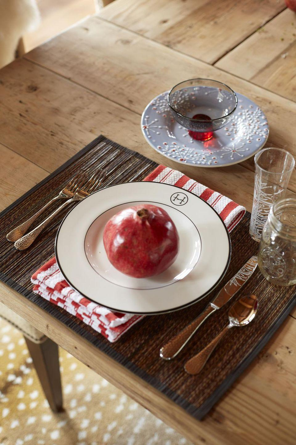 """<p>The end of fall is the peak season for pomegranates, so why not incorporate the fruit into a simple, yet elegant, place setting? Interior designer <a href=""""https://janiemolster.com/"""" rel=""""nofollow noopener"""" target=""""_blank"""" data-ylk=""""slk:Janie Molster"""" class=""""link rapid-noclick-resp"""">Janie Molster</a> paired the fruit with a simple white plate and striped cloth napkin for a perfect fall dining table look. </p>"""