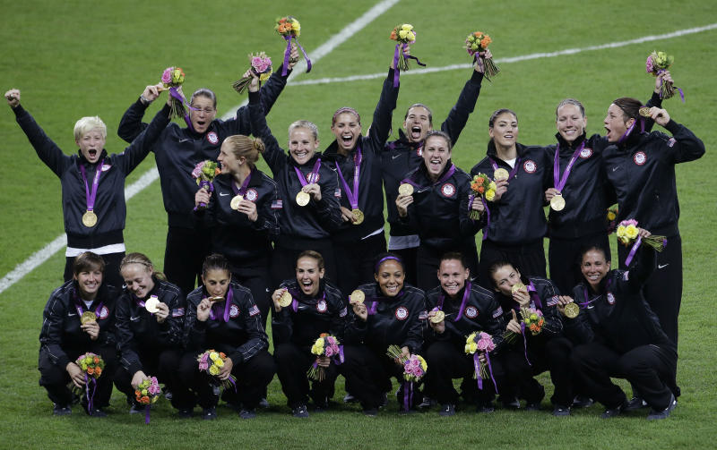 United States gold-medalist women's soccer players celebrate with their medals after winning the women's soccer final against Japan at the 2012 Summer Olympics, Thursday, Aug. 9, 2012, in London.  The United States won 2-1. (AP Photo/Andrew Medichini)