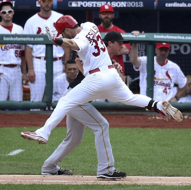 St. Louis Cardinals' Daniel Descalso tries to elude Pittsburgh Pirates pitcher Tony Watson, but Watson tags him out to end the seventh inning during Game 2 of the National League division series, Friday, Oct. 4, 2013, in St. Louis. The Pirates won 7-1. (AP Photo/St. Louis Post-Dispatch, Chris Lee)