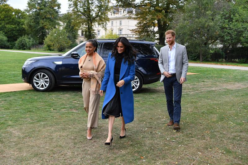 Meghan, Duchess of Sussex (C) arrives with her mother, Doria Ragland (L) and Britain's Prince Harry, Duke of Sussex to host an event to mark the launch of a cookbook with  recipes from a group of women affected by the Grenfell Tower fire at Kensington Palace in London on September 20, 2018. (Photo by Ben STANSALL / POOL / AFP)        (Photo credit should read BEN STANSALL/AFP/Getty Images)