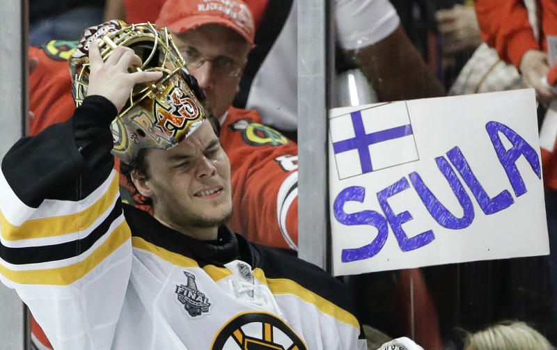 Boston Bruins goalie Tuukka Rask (40) puts his mask back on after a break in the third period against the Chicago Blackhawks as a fan holds up a sign in Finnish calling Rask a hockey sieve in English, during Game 5 of the NHL hockey Stanley Cup Finals, Saturday, June 22, 2013, in Chicago. (AP Photo/Nam Y. Huh)