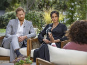 "This image provided by Harpo Productions shows Prince Harry, left, and Meghan, Duchess of Sussex, in conversation with Oprah Winfrey. ""Oprah with Meghan and Harry: A CBS Primetime Special"" airs March 7, 2021. Britain's royal family and television have a complicated relationship. The medium has helped define the modern monarchy: The 1953 coronation of Queen Elizabeth II was Britain's first mass TV spectacle. Since then, rare interviews have given a glimpse behind palace curtains at the all-too-human family within. (Joe Pugliese/Harpo Productions via AP, File)"