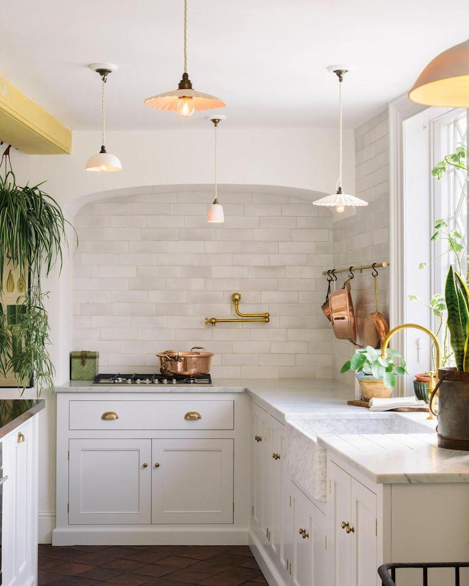 """<p>This white kitchen nods to a quintessential country kitchen style, displaying classic copper pots and pans, plenty of plants, shaker style cabinets, and mixing in charming and unexpected elements like mismatched pendant lights.</p><p>Pictured: <a href=""""https://www.devolkitchens.co.uk/shop/lighting"""" rel=""""nofollow noopener"""" target=""""_blank"""" data-ylk=""""slk:Lighting by deVOL"""" class=""""link rapid-noclick-resp"""">Lighting by deVOL</a></p>"""