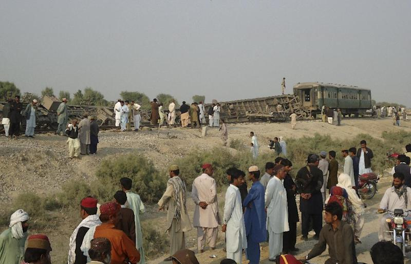 Pakistanis gather at the site of a deadly bomb blast that hit a train, in Kashmor district, Pakistan, Sunday, Feb. 16, 2014. A bomb placed by an ethnic separatist group derailed a train in southwest Pakistan on Sunday, killing several people including children, and wounding tens more police and the militants said. (AP Photo/Fida Hussain)