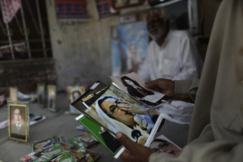A Pakistani man looks at photographs of Pakistan's slain leader Benazir Bhutto, while displayed for sale by vendor, Mohammed Ashraf, 65, at the site where she was killed, in Rawalpindi, Pakistan, Monday, April 8, 2013. Pakistan's top court on Monday ordered former military ruler Gen. Pervez Musharraf to respond to allegations that he committed treason while in power and barred him from leaving the country. The Taliban have threatened to kill him, and he faces a series of legal charges that he has denied, including some related to the 2007 assassination of former Prime Minister Benazir Bhutto. (AP Photo/Muhammed Muheisen)