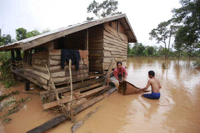 <p>Kongvilay Inthavong and his wife Thongla clean up their house as the floodwaters start to recede i in Sanamxay district, Attapeu province, Laos on Thursday, July 26, 2018. (Photo: Hau Dinh/AP) </p>