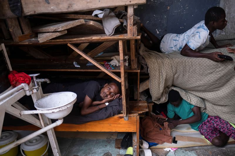 People shelter inside a school after their settlement was burned down by gangs, in Port-au-Prince