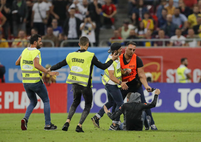 A fan is detained by stewards after entering the pitch during the Euro 2020 group F qualifying soccer match between Romania and Spain, at the National Arena stadium in Bucharest, Romania, Thursday, Sept. 5, 2019. (AP Photo/Vadim Ghirda)