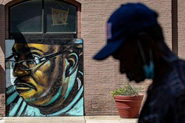 PHOTO: A pedestrian walks past a mural of David McAtee, June 3, 2020, painted by artist Damon Thompson on plywood outside the Limbo Tiki Bar in downtown Louisville, Ky. McAtee was shot and killed during a confrontation with police June 1, 2020. (Courier Journal via USA Today Network)